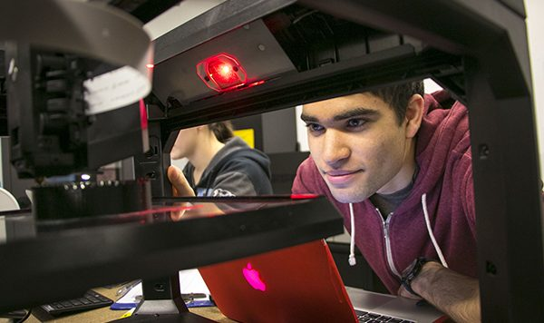 Student peers at the 3D printer output